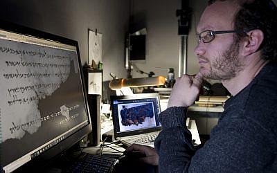 Oren Ableman, scroll researcher at the Dead Sea Scrolls unit of the Israel Antiquities Authority, examining the ink traces that have been discovered. (Shai Halevi, The Leon Levy Dead Sea Scrolls Digital Library)