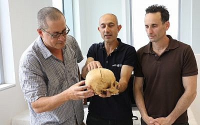 Researchers who are studying the first evidence of blood vengeance, discovered in a cave in the Jerusalem Hills. From left to right: Prof. Boaz Zissu Dr. Yossi Nagar and Dr. Haim Cohen with the skull (Chen Galili/Israel Antiquities Authority)