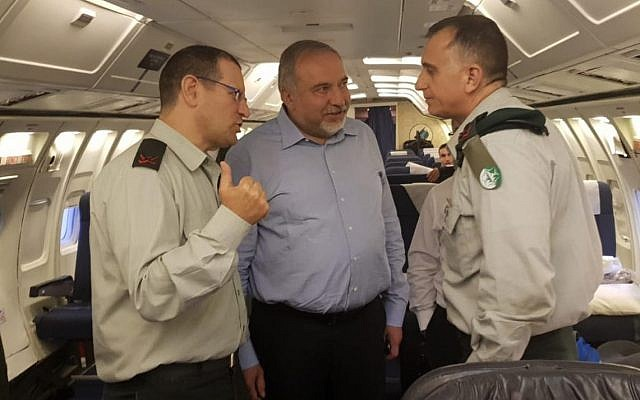 Defense Minister Avigdor Liberman speaks with his military secretary Brig. Gen. Yair Kohls, left, and the head of Military Intelligence Maj. Gen. Tamir Hyman, right, during a flight to Moscow on May 30, 2018. (Ariel Hermoni/Defense Ministry)