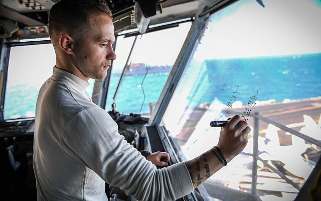 US Navy Airman Zackary Knabe writes down aircraft identifiers on primary flight control room window aboard the aircraft carrier USS Theodore Roosevelt (CVN 71) in the Persian Gulf on January 4, 2018. (US Navy/ Spencer Roberts)