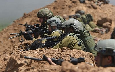 File: IDF soldiers monitor the Gaza security fence during violent protests along the border on May 14, 2018. (Israel Defense Forces)