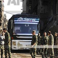 In this photo released on April 30, 2018, by the Syrian official news agency SANA, Syrian government forces gather in front of a bus carries al-Qaida-linked fighters during an evacuation from the Palestinian refugee camp of Yarmouk, near Damascus, Syria. (SANA via AP)