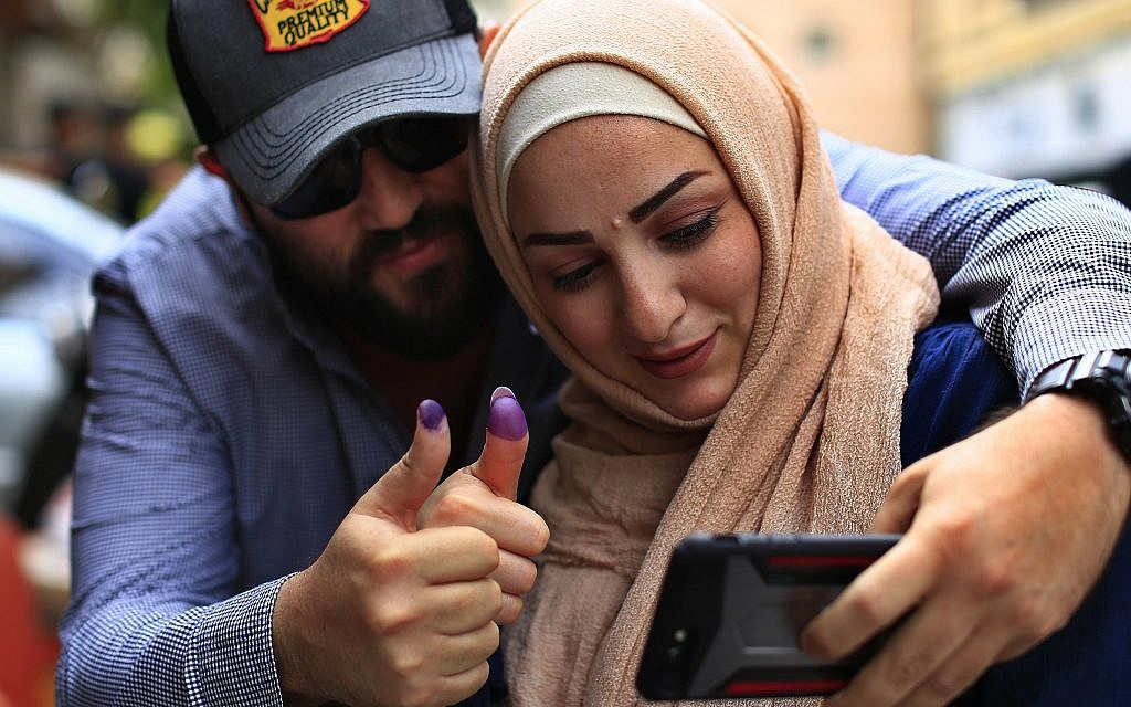 A couple take a selfie as they display their ink-stained fingers after casting their votes during Lebanon's parliamentary elections in Beirut, Lebanon, Sunday, May 6, 2018 (AP Photo/Hassan Ammar)
