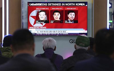 In this May 3, 2018 photo, people watch a TV news report screen showing portraits of three Americans, Kim Dong Chul, left, Tony Kim and Kim Hak Song, right, detained in the North Korea, at the Seoul Railway Station in Seoul, South Korea. (AP Photo/Ahn Young-joon)