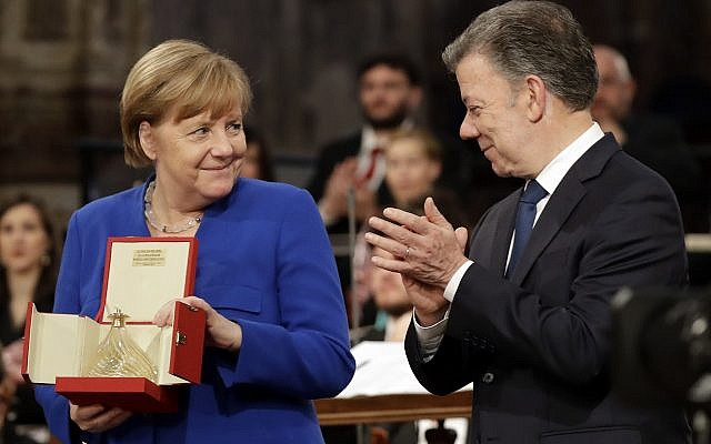 German Chancellor Angela Merkel, left, flanked by Colombian President Juan Manuel Santos, holds the St. Francis lamp peace prize she received by Father Mauro Gambetti during a ceremony inside Assisi's Basilica, Italy, Saturday, May 12, 2018. (AP Photo/Alessandra Tarantino)