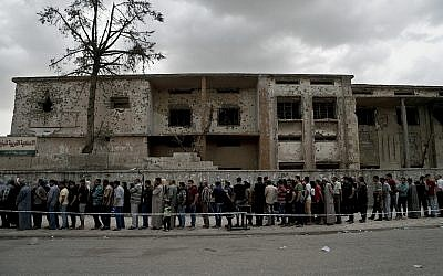 Iraqis wait in a long line to cast their vote in the country's parliamentary elections at a polling site in a battle-damaged building in west Mosul, Iraq, Saturday, May 12, 2018.(AP/Maya Alleruzzo)