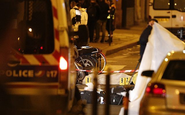 A dead body under a blanket after a knife attack that left at least two dead including the assailant in central Paris, early Sunday May 13, 2018. (AP Photo/Thibault Camus)