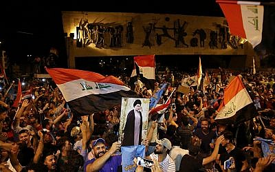 Followers of Shiite cleric Muqtada al-Sadr, displayed on the poster, celebrate in Tahrir Square, Baghdad, Iraq, early Monday, May 14, 2018. (Karim Kadim/AP)