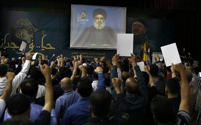 Hezbollah leader Sheik Hassan Nasrallah speaks on a screen via a video link during a ceremony to mark the second anniversary of the death of Hezbollah top commander, Mustafa Badreddine, who was killed in an explosion in Damascus, in the southern suburbs of Beirut, Lebanon, Lebanon, on May 14, 2018. (AP Photo/Bilal Hussein)