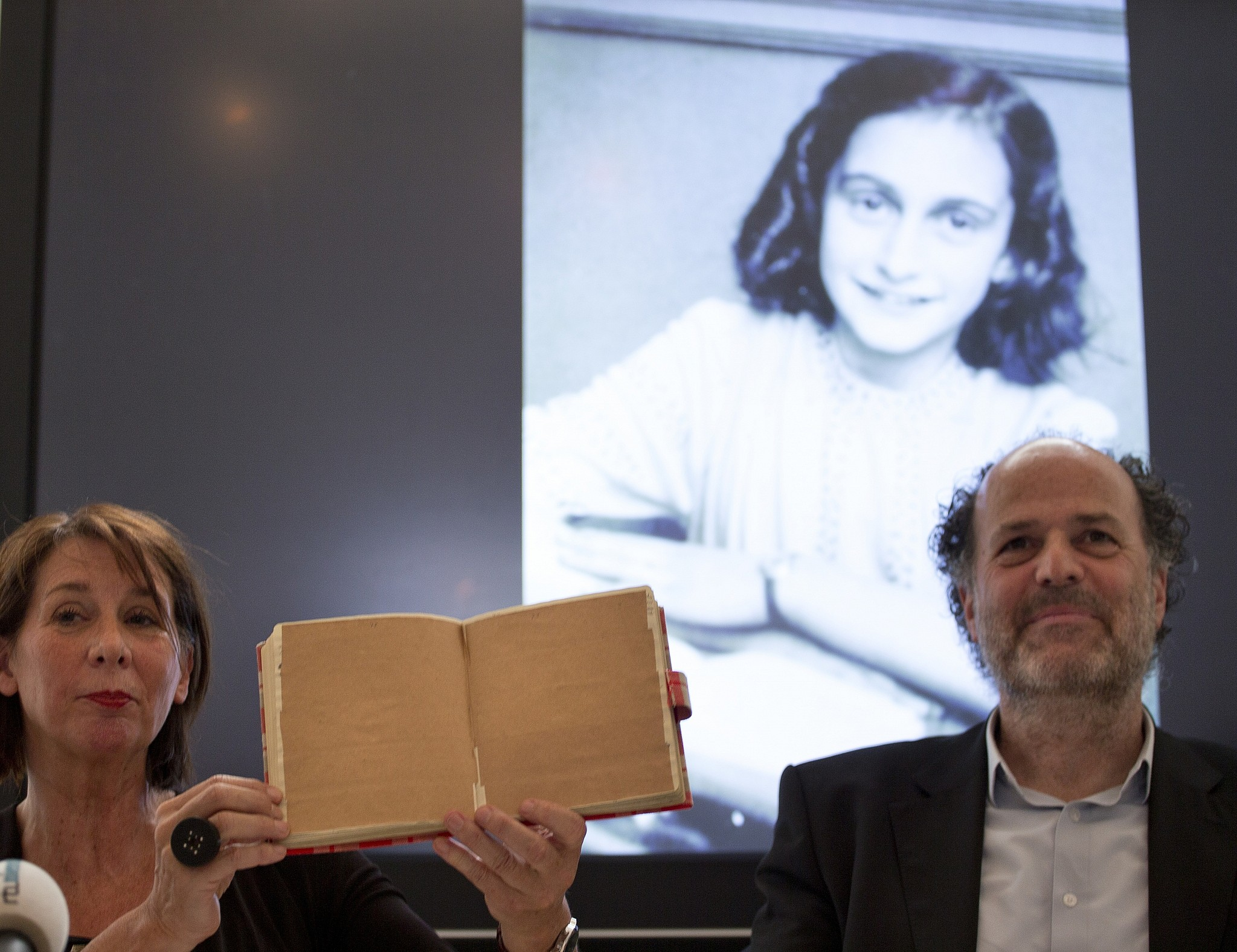 Teresien da Silva left and Ronald Leopold of the Anne Frank Foundation show a facsimile of Anne Frank's diary with two pages taped off during a press conference at the foundation's office in Amsterdam Netherlands Tuesday