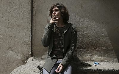 In this Sunday, April 22, 2018 photo, Nahal, a 19-year-old transgender woman, smokes a cigarette on her balcony in Tehran, Iran. (AP Photo/Vahid Salemi)