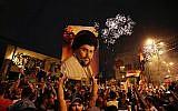 Followers of Shiite cleric Muqtada al-Sadr, seen in the poster, celebrate in Tahrir Square, Baghdad, Iraq, early Monday, May 14, 2018 (AP Photo/Hadi Mizban)