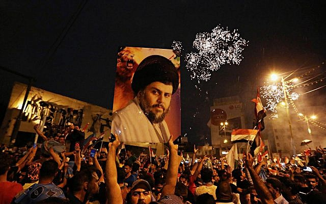 Followers of Shiite cleric Muqtada al-Sadr, seen in the poster, celebrate in Tahrir Square, Baghdad, Iraq, early Monday, May 14, 2018 (AP Photo/Hadi Mizban)