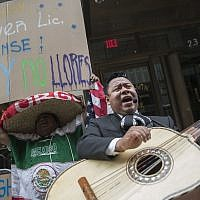 A demonstrator dances and sings along the Mariachi Tapatio de Alvaro Paulino band as they perform during a demonstration across the street from the building that once housed the office space of Aaron Schlossberg, Friday, May 18, 2018, in New York. (AP /Mary Altaffer)