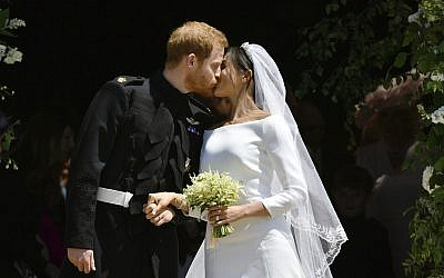Britain's Prince Harry, Duke of Sussex kisses his wife Meghan, Duchess of Sussex as they leave from the West Door of St George's Chapel, Windsor Castle, in Windsor, on May 19, 2018 after their wedding ceremony. (Ben Birchhall, Pool/via AP)