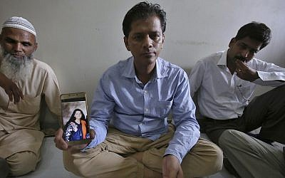 Abdul Aziz Sheikh, center, father of Sabika Sheikh, a victim of a shooting at a Texas high school, shows a picture of his daughter in Karachi, Pakistan, Saturday, May 19, 2018. (AP Photo/Fareed Khan)