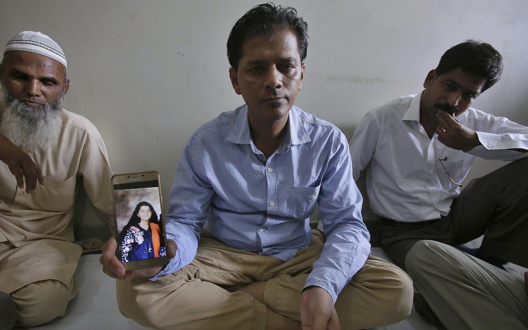 Abdul Aziz Sheikh, center, father of Sabika Sheikh, a victim of a shooting