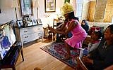 Jenice Armstrong of Burlington, N.J. takes a photo during a television viewing party of the royal wedding of Meghan Markle and Prince Harry , Saturday, May 18, 2018, at the Armstrong-Turner residence in Burlington, N.J. (AP Photo/Corey Perrine)