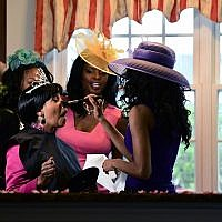 Paula Jackson of Philadelphia, left, receives makeup from makeup artist Pietra Dunmore, right, while Jenice Armstrong of Burlington, N.J. looks on during a television viewing party of the royal wedding of Meghan Markle and Prince Harry Saturday, May 18, 2018, at the Armstrong-Turner residence in Burlington, N.J. (AP Photo/Corey Perrine)