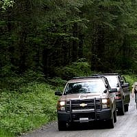 Washington State Fish and Wildlife Police leave the scene on a remote King County road near the site of a fatal cougar attack in East King County, Washington, May 19, 2018. (Alan Berner/The Seattle Times via AP)