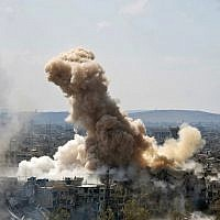 In this file photo released on Sunday, April 22, 2018 by the Syrian official news agency SANA, smoke rises after Syrian government airstrikes and shelling hit in Hajar al-Aswad neighborhood held by Islamic State militants, southern Damascus, Syria.  (SANA via AP)