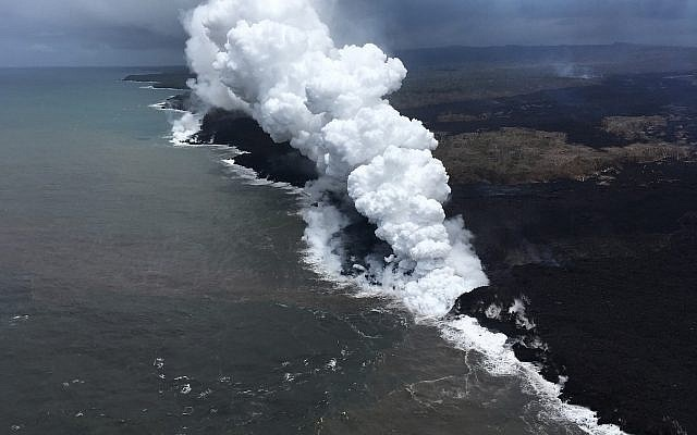 Lava sends up clouds of steam and toxic gases as it enters the Pacific Ocean as Kilauea Volcano continues its eruption cycle near Pahoa on the island of Kilauea, Hawaii, May 26, 2018. (US Geological Survey via AP)
