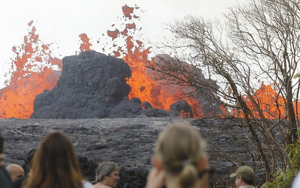 In a May 26, 2018 photo, area residents, the media and national guard flock to what is now the end of Leilani Avenue to take in the fiery show at fissures 2, 7 and 8 of the Kilauea volcano near Pahoa. (George F. Lee/The Honolulu Advertiser via AP)