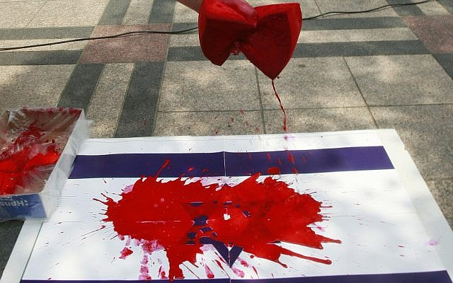 Illustrative photo of an Israeli flag daubed with red paint. (Ahn Young-joon/AP)