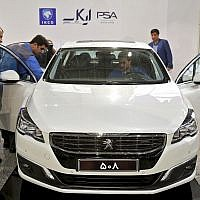 Workers inspect a Peugeot 508 at the Iran Khodro car factory in Tehran, Iran, October 5, 2016. (AP Photo/Ebrahim Noroozi)