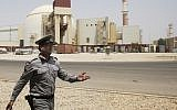 An Iranian security officer directs media at the Bushehr nuclear power plant, with the reactor building seen in the background, just outside the southern city of Bushehr, Iran, August 21, 2010. (AP Photo/Vahid Salemi, File)