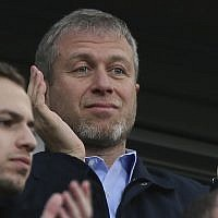 Chelsea's Russian owner Roman Abramovich applauds his players after they defeated Arsenal 6-0, in an English Premier League soccer match at Stamford Bridge stadium in London, March 22, 2014. (AP Photo/Alastair Grant)
