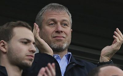In this March 22, 2014, photo, Chelsea's Russian owner Roman Abramovich applauds his players after they defeated Arsenal 6-0 in an English Premier League soccer match at Stamford Bridge stadium in London. (AP Photo/Alastair Grant)