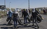 File: Masked Palestinian protesters carry tires to be set on fire, during clashes with Israeli troops, at the northern entrance of the West Bank city of Ramallah, March 12, 2018 (AP Photo/Nasser Nasser)
