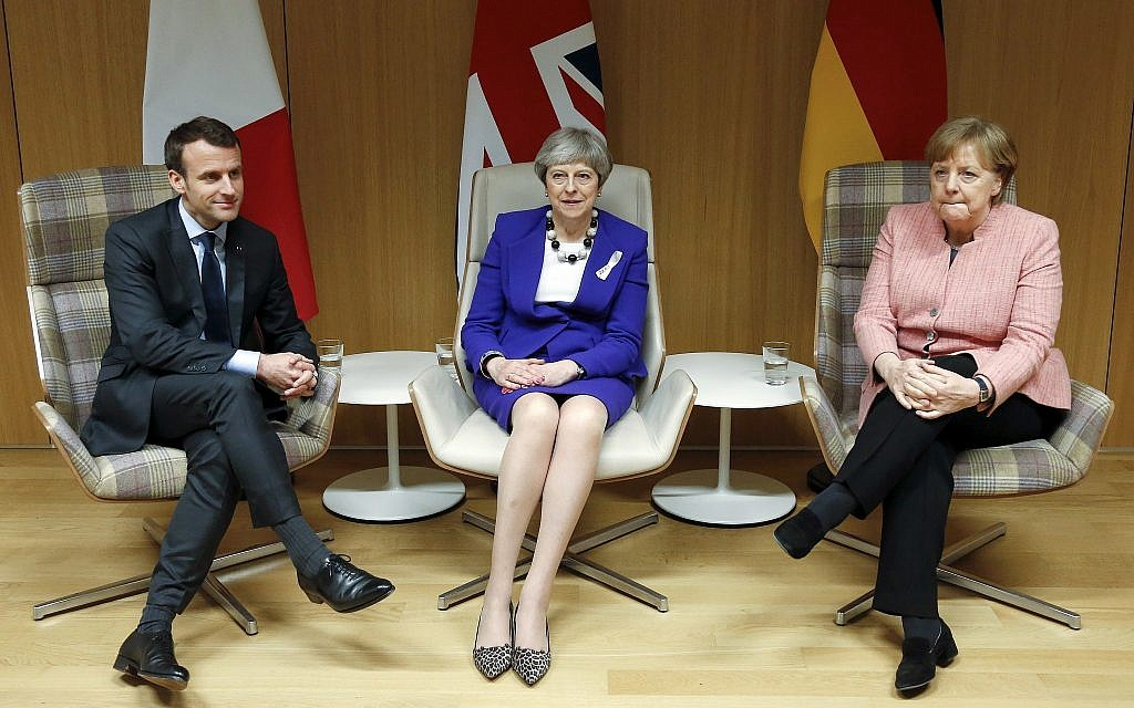 British Prime Minister Theresa May, center, German Chancellor Angela Merkel, right, and French President Emmanuel Macron, left, meet on the sidelines of an EU summit at the Europa building in Brussels on Thursday, March 22, 2018. (Francois Lenoir, Pool Photo via AP)
