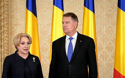 Romanian Prime Minister Viorica Dancila, left, stands next to Romania's President Klaus Iohannis, after the swearing in of her cabinet, in Bucharest, Romania, on January 29, 2018. (AP/Vadim Ghirda)