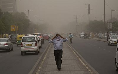 In this May 2, 2018, file photo, a man wraps a scarf around his nose as a dust storm envelops the city in New Delhi, India. (AP Photo/Manish Swarup, File)