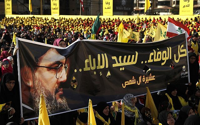 """In this photo from April 13, 2018, supporters of Hezbollah leader Sayyed Hassan Nasrallah hold a banner with his portrait and Arabic words that read: """"All the loyalty to the man of nobility."""" (AP/Hussein Malla)"""