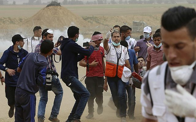 Palestinian medics and protesters evacuate a wounded man during a protest at the Gaza Strip's border with Israel, east of Khan Younis, on May 4, 2018. (AP Photo/Adel Hana)