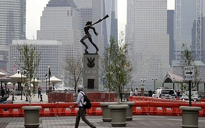 A man walks in front of a statue dedicated to the victims of the Katyn massacre of 1940, Friday, May 4, 2018, in Jersey City, N.J.  (AP Photo/Julio Cortez)