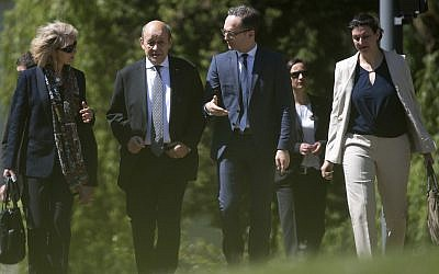 French foreign minister Jean-Yves Le Drian, second left, and his German counterpart Heiko Maas, third from left, take a stroll in the park of Villa Borsig in Berlin, Monday, May 7, 2018. (Ralf Hirschberger/dpa via AP)