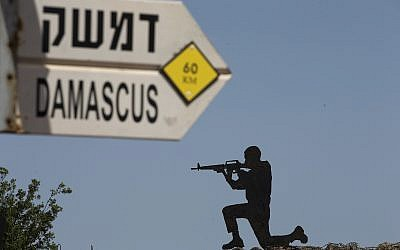 A mock road sign for Damascus, the capital of Syria, and a cutout of a soldier, are displayed in an old outpost in the Golan Heights near the border with Syria, May 10, 2018. (AP Photo/Ariel Schalit)