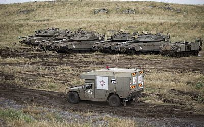 An Israeli military ambulance drives past tanks in the Golan Heights, near the border with Syria, May 10, 2018. (AP Photo/Ariel Schalit)