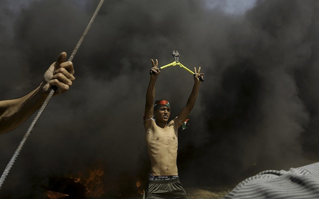 A Palestinian protester holds bolt cutters amid black smoke from burning tires near the fence during a protest at the Gaza Strip's border with Israel, May 11, 2018.  (AP Photo/Adel Hana)