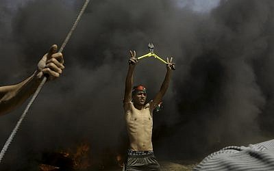 A Palestinian protester holds wire cutters amid black smoke from burning tires near the fence during a protest at the Gaza Strip's border with Israel, May 11, 2018.  (AP Photo/Adel Hana)