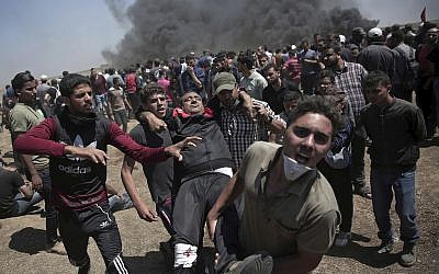 Palestinians carry an injured man who was shot by Israeli troops during a deadly protest at the Gaza Strip's border with Israel, east of Khan Younis, on May 14, 2018. (AP Photo/Khalil Hamra)