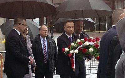 The president of Poland, Andrzej Duda, center, carries a bouquet of roses toward the waterfront statue commemorating the 1940 Soviet massacre of Poles, Wednesday, May 16, 2018. (AP Photo/David Porter)