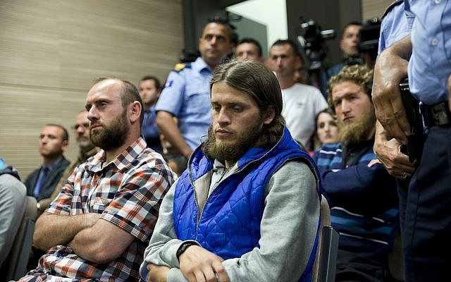 Kosovo police officers stand guard next to from left, Kenan Plakaj, Arton Ahmeti, center, and Leotrim Musliu, second row right, in court for the foiled attack against the Israeli team in a 2016 qualifying World Cup match in neighboring Albania, in Kosovo's capital Pristina on Friday, May 18, 2018. (AP Photo/Visar Kryeziu)