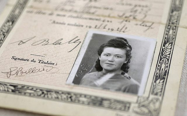 """In this Monday, May 21, 2018, photo, a World War II-era, black-and-white photograph of French student Simone Billard is attached to a fake identity card created by the French Resistance in an exhibit called """"Women in WWII: On the Home Fronts and the Battlefronts"""" at The International Museum of World War II, in Natick, Massachusetts. (AP Photo/Steven Senne)"""