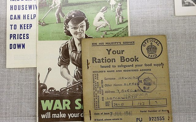 In this Monday, May 21, 2018, photo, a World War II British ration card, right, rests on a flyer, center, that shows a woman operating machinery juxtaposed with a depiction of a family doing yard work, in a display at The International World War II Museum, in Natick, Mass. (AP Photo/Steven Senne)
