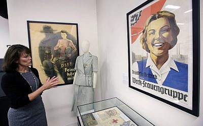 In this Monday, May 21, 2018, photo, Sue Wilkins, director of education at The International Museum of World War II, in Natick, Mass., stands near a 1933 propaganda poster, right, that praised the Nazi organization German Labor Front, which was created after the Nazis eliminated trade unions. (AP Photo/Steven Senne)
